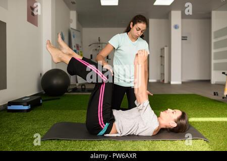 Thérapeute physique aider young caucasian woman avec l'exercice au cours de la réadaptation dans le gymnase de l'hôpital. Une formation de physiothérapeute femelle patients Banque D'Images