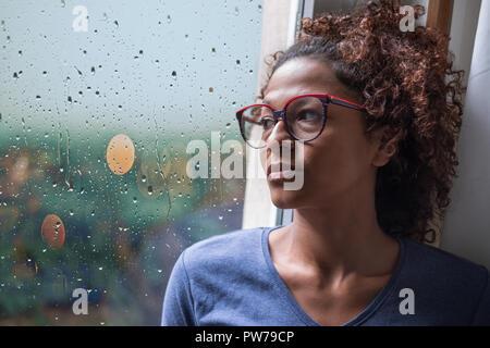 Triste african american girl en regardant par la fenêtre de temps de pluie
