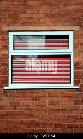 Store vénitien rouge et gris dans une fenêtre de la chambre Banque D'Images
