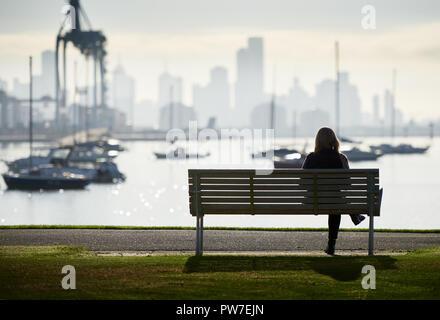 Femme seule en silhouette assise sur un banc en bord de l'eau avec des bateaux et sur les toits de la ville en arrière-plan. Banque D'Images