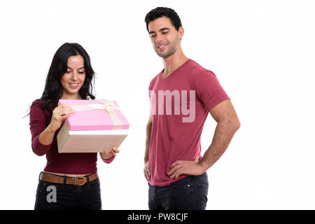 Young happy couple smiling while woman opening gift box et l'homme Banque D'Images