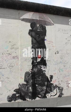L'article de l'East Side Gallery - Berlin mur recouvert de graffitis et stencil art de garçon et de jeune fille Banque D'Images
