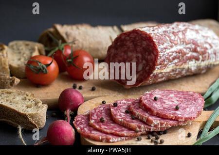 Morceaux de saucisses, pommes de terre et le pain isolé sur fond sombre Banque D'Images