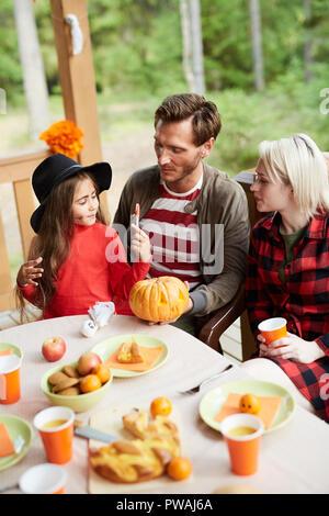 Famille de jeunes parents et leur adorable fille assis par table d'halloween et de discuter des symboles de l'appartement de vacances Banque D'Images