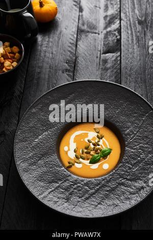 Soupe de carottes et de potiron avec les graines de citrouille, crème et basilic en noir sur plaque moderne en bois table avec copie espace. Dark style moderne. Vue d'en haut. Banque D'Images