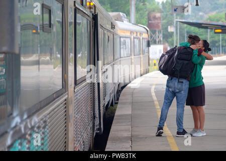 Deux personnes serrant en disant au revoir à l'un l'autre avant de s'embarquer dans un train à une gare ferroviaire de la plate-forme Banque D'Images