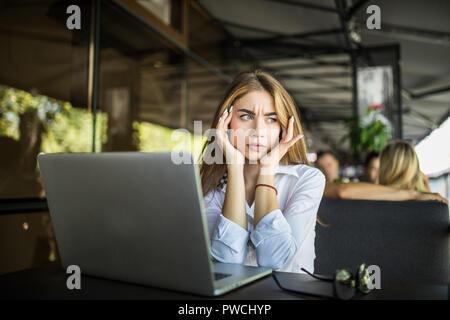 Une étudiante a souligné avoir maux touchant la préparation des temples pour les tests en cafe, fille millénaire frustré se sent fatigué ou nerveux, peur de l'examen Banque D'Images
