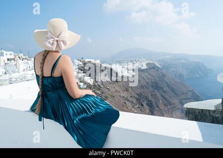 Happy woman in robe vert et chapeau de soleil profitant de ses vacances à Santorin, Grèce. Vue sur la caldeira et la mer Égée d'Imerovigli.