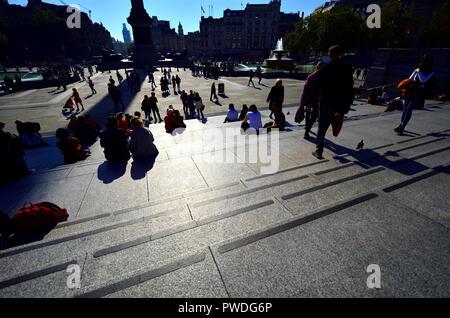Des gens assis Trafalgar Square, Londres, Angleterre, Royaume-Uni. Éclairé par led Banque D'Images
