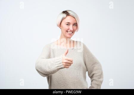 Portrait de belle femme avec des cheveux courts teints avec Thumbs up sign. Elle est d'approuver votre choix. Banque D'Images
