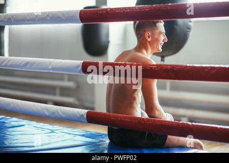 L'homme athlétique repose en anneau et rit. Pause dans le sport. Se détendre avant Boxer lutte Banque D'Images