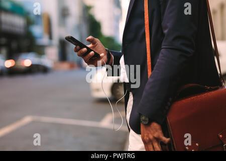 Cropped shot of businessman outdoors en utilisant le téléphone mobile. Sac à main man walking on city street avec téléphone cellulaire dans la main. Banque D'Images