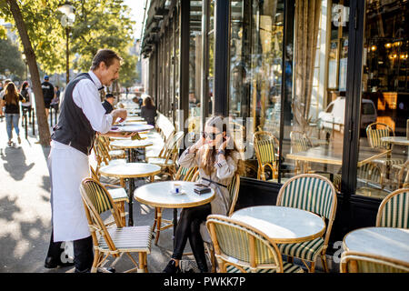 PARIS, FRANCE - 31 août 2018: du café pour une jeune femme assise à la clientèle française traditionnelle en plein air à Paris