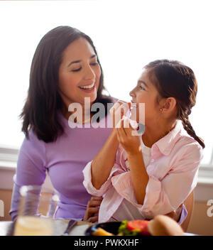 Heureuse mère et sa fille souriant à la table de dîner. Banque D'Images