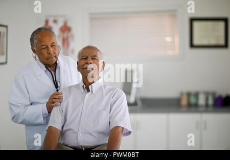 Man ayant ses battements écouté par un médecin de sexe masculin à l'intérieur d'un bureau. Banque D'Images