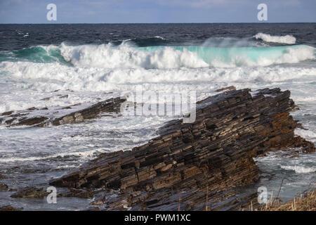 D'énormes vagues aqua avec mousse blanche rouler dans un rivage rocailleux au point d'Buckquoy près de Birsay, Orkney Ecosse lors d'une journée ensoleillée, avec flying spray Banque D'Images