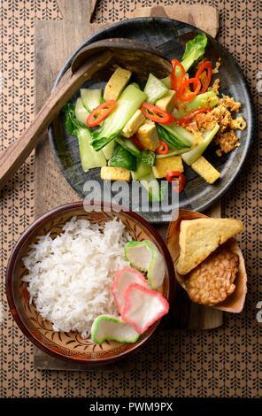 Sawi Tumis Hijau (Indonesian sauté de bok choy) servi le riz blanc, le tempeh et le tofu Banque D'Images