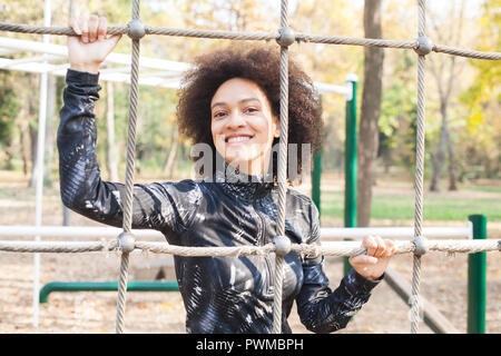 Portrait Of Beautiful Smiling Mixed Race Woman at Outdoor Exercice Fitness Park In Sportswear avec coiffure Afro