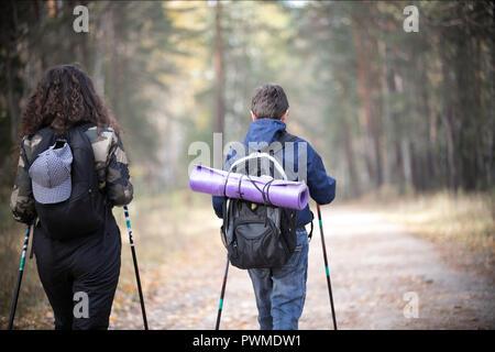 La marche nordique. Portrait d'enfant et femme bouclés dans un automne. Enfant et de la femme s'amusant dans le parc automne ensoleillé. Vue arrière