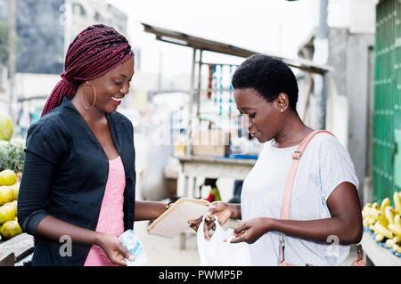 Heureux les jeunes femmes à la recherche du marché dans un sac contenant des fruits. Banque D'Images
