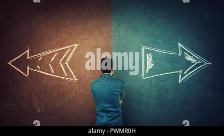 Perplexe d'affaires et un tableau noir split avec flèches de deux façons différentes, côté rouge et bleu. Bon choix entre gauche et droite, l'échec o Banque D'Images