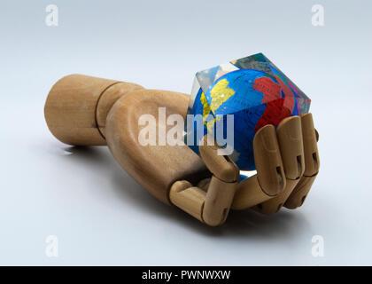 Une main en bois holding Earth