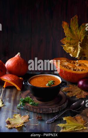 Soupe au potiron purée avec les verts dans une assiette sur une table. Sur l'arrière-plan de citrouilles et Menu restaurant concept Copy space Banque D'Images