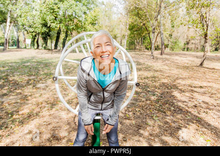 Portrait of Senior Woman sain entraînement à la salle de sport en plein air dans la nature. En riant et en regardant la caméra.