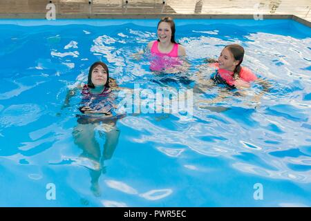Le groupe de 3 teenage girlfriends having fun in swimming pool Banque D'Images