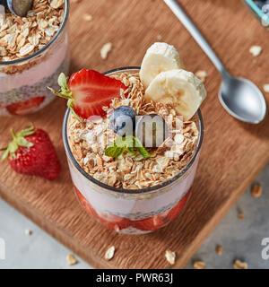 Le verre avec des flocons d'avoine, banane, fraises, fruits, graines de chia smoothie frais sur une planche de bois. Banque D'Images