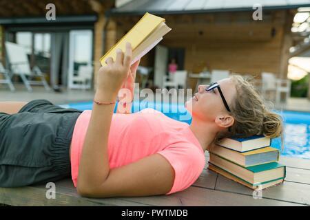 Jeune fille dans les verres près de la piscine avec une pile de livres, la lecture de livre. L'éducation, la connaissance, l'été Banque D'Images