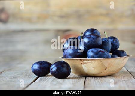 Les prunes fraîches dans un bol sur fond de bois Banque D'Images