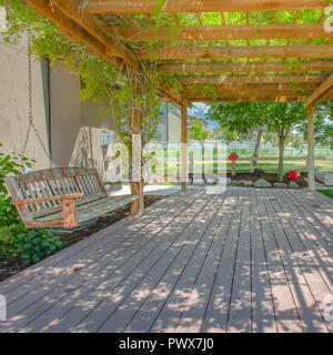La pendaison Swing sur une pergola sur une terrasse en bois Banque D'Images