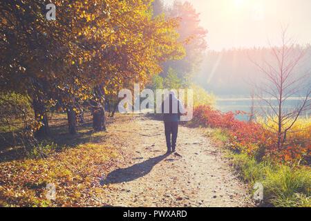 Un homme marche le long d'un chemin dans un parc près d'un lac au petit matin à l'automne