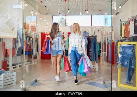 Vue avant du happy female friends sortir ensemble de vêtements boutique en centre commercial. Les jeunes filles attrayantes à l'un l'autre et rire après le shopping. Notion de plaisir et de bonheur. Banque D'Images