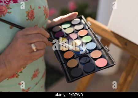 Senior woman painting on canvas dans le jardin Banque D'Images