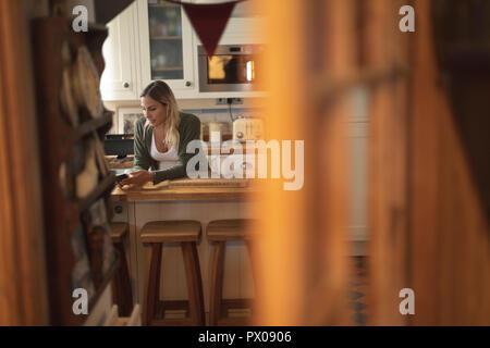 Pregnant woman texting on le téléphone dans la cuisine