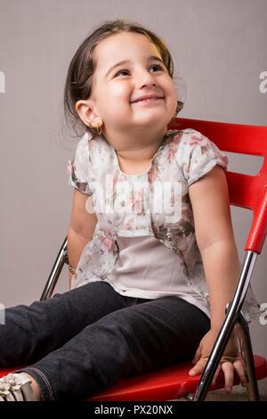 Jeune fille de deux ans, peu de place sur un fauteuil rouge en face de l'arrière-plan gris, vertical shot Banque D'Images