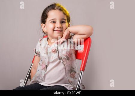 Jeune fille de deux ans, peu de place sur un fauteuil rouge en face de l'arrière-plan gris Banque D'Images