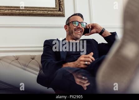 Portrait of mature relaxant businessman sitting on couch et parlant au téléphone. Man relaxing in chambre d'hôtel et faire appel. Banque D'Images