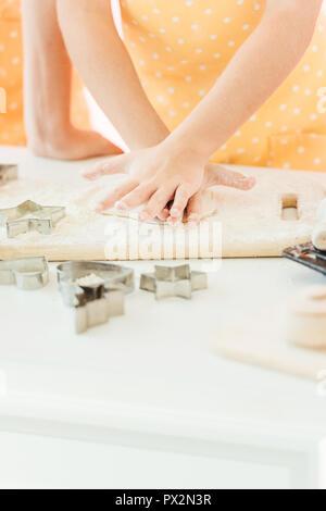 Cropped shot of little girl couper la pâte en différentes formes pour les cookies avec la mère Banque D'Images