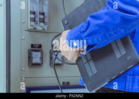 Les ingénieurs sont des hommes contrôle du circuit électrique par programme dans l'ordinateur portable.