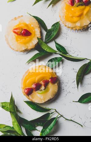 Mise à plat de fruits et des tartes aux fruits et feuilles fraîches sur fond blanc. Banque D'Images