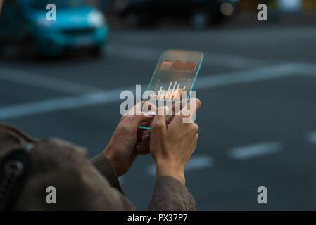 Gros plan sur une femme main qui tient un concept gadget téléphone transparent, à l'aide d'une application avec des données charte graphique