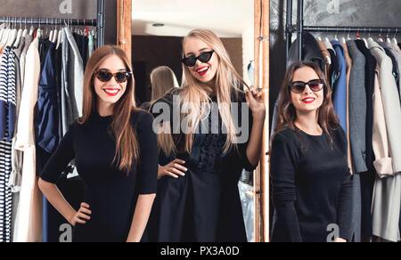 Trois copines sur le shopping dans la boutique de mode, concept vendredi noir Banque D'Images