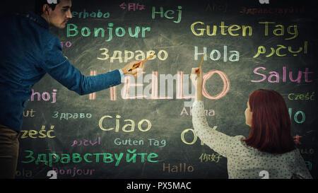 L'homme et de la femme ensemble dimensions mot bonjour dans différentes langues et de couleurs sur tableau noir. Occasion d'apprentissage de langues pour les étudiants. Busin Banque D'Images