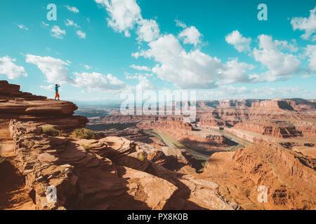 Un jeune randonneur est debout sur le bord d'une falaise offrant une vue spectaculaire sur la célèbre rivière Colorado, Dead Horse Point State Park, Utah, USA Banque D'Images