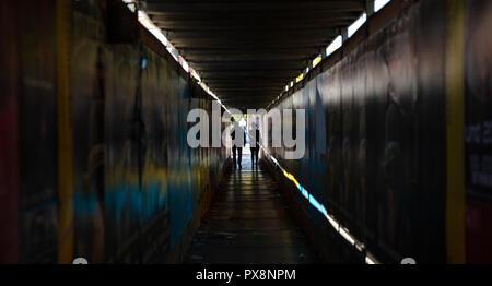 La lumière au bout du tunnel. Jeune couple en train de marcher dans un sombre couloir de protection pour les piétons Banque D'Images
