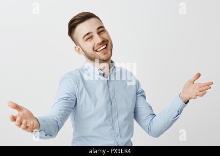Guy étant heureux salutation meilleur ami félicitant avec bonne affaire soulevant palmiers dans l'accueil chaleureux sourire geste amical avec délectation debout dans fromal shirt et jeans bleu Banque D'Images