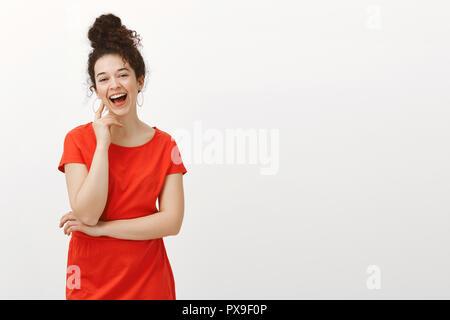 Portrait de l'insouciance heureuse fille européenne dans rouge tendance robe avec des cheveux bouclés peignées à bun, Laughing Out Loud et toucher le visage avec la main, en parlant avec des amis, sortir en ville cafe sur mur gris Banque D'Images